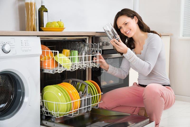 Mujer que toma el vidrio de consumición del lavaplatos fotografía de archivo