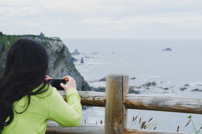 Mujer que toma imágenes con el teléfono celular de un paisaje marítimo imagenes de archivo