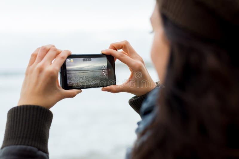 Mujer que toma imágenes con Nokia Lumia 1020 imagen de archivo libre de regalías