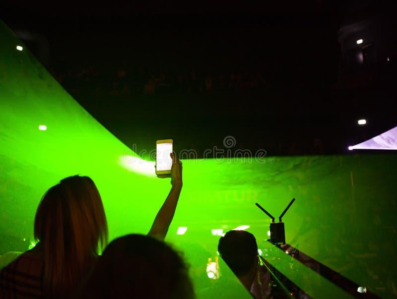 mujer que toma imágenes en un acontecimiento con un smartphone contra luces de neón verdes imagen de archivo libre de regalías