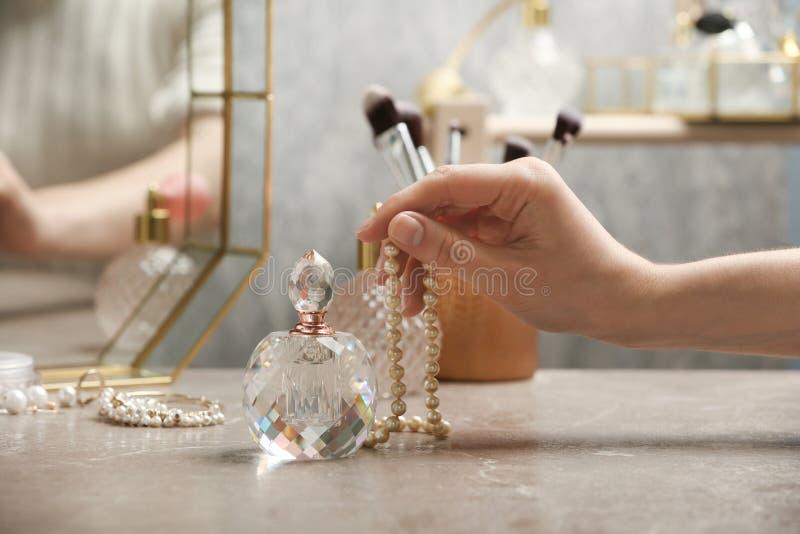 Mujer que toma la botella cristalina de perfume lujoso del tocador, primer imágenes de archivo libres de regalías