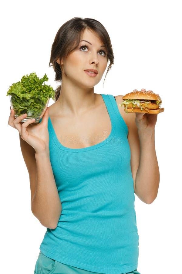 Mujer que toma la decisión entre la ensalada sana y los alimentos de preparación rápida fotografía de archivo libre de regalías
