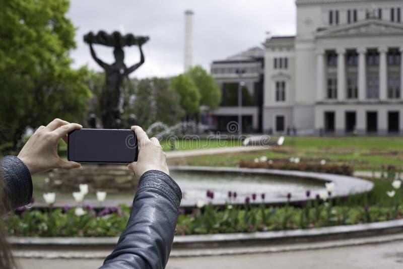 Mujer que toma la foto con el teléfono celular móvil fotografía de archivo libre de regalías