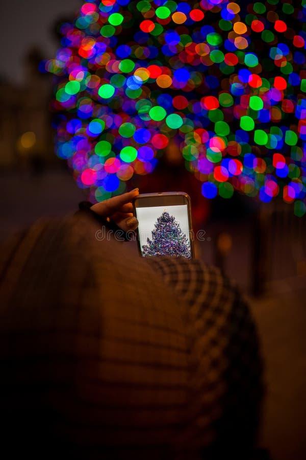 Mujer que toma la foto con el teléfono celular móvil foto de archivo