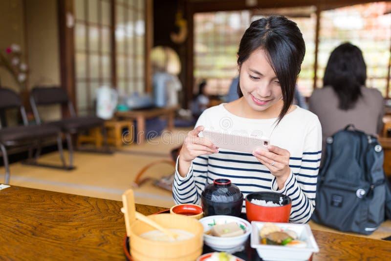Mujer que toma la foto con el teléfono móvil en su comida imágenes de archivo libres de regalías
