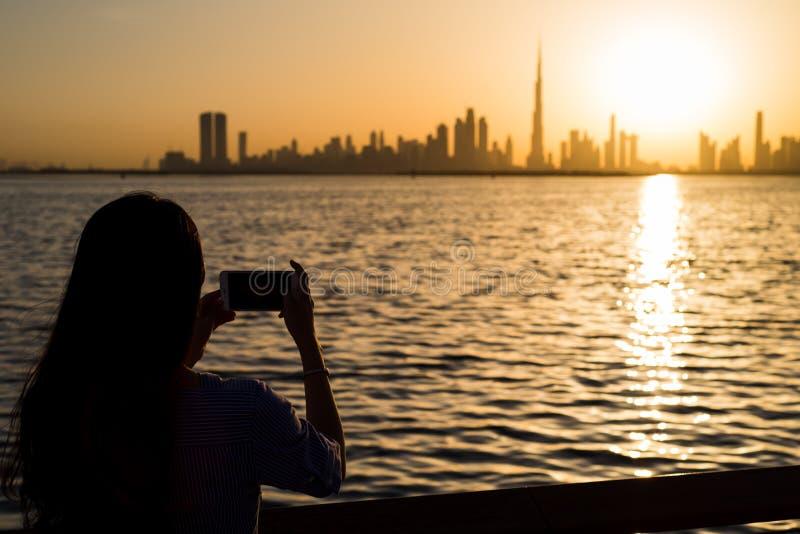 Mujer que toma la foto de Dubai en la puesta del sol foto de archivo libre de regalías