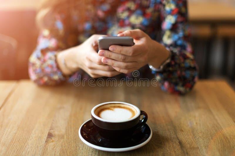Mujer que toma la foto del café con smartphone fotografía de archivo libre de regalías