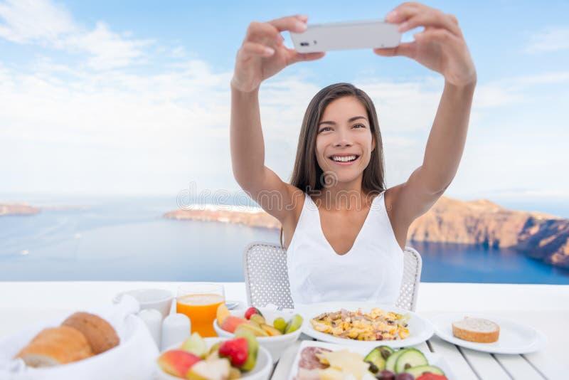 Mujer que toma la foto del desayuno en el teléfono elegante App fotografía de archivo libre de regalías