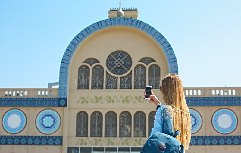 Mujer que toma la foto móvil del Souq central en la ciudad de Sharja, U imagenes de archivo