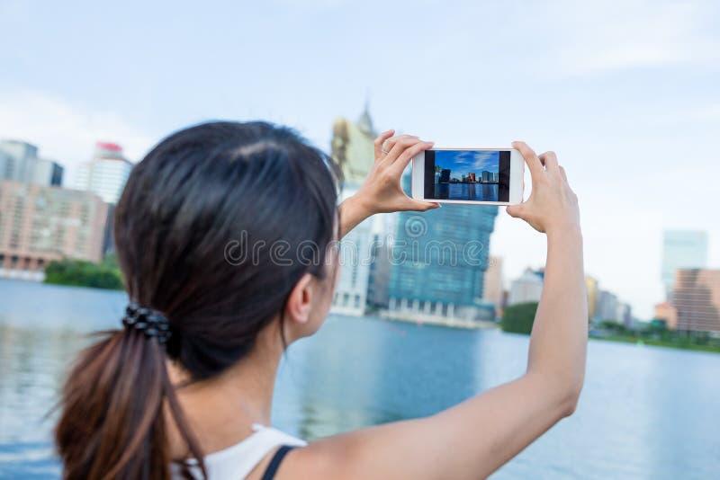 Mujer que toma la foto por el teléfono móvil fotografía de archivo libre de regalías