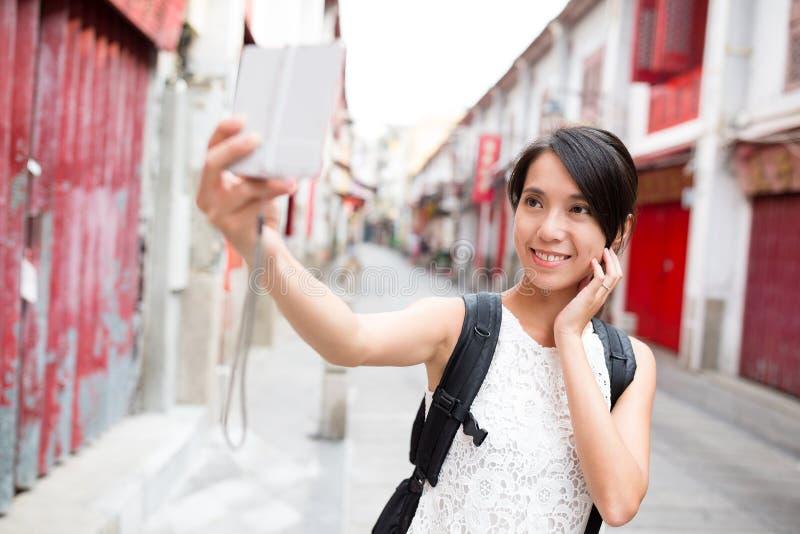 Mujer que toma la foto por la cámara digital en la ciudad vieja de Macao fotos de archivo libres de regalías