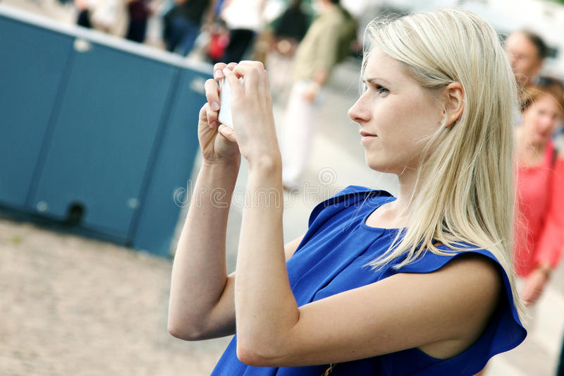 Mujer que toma la imagen con el teléfono móvil en la calle imagenes de archivo