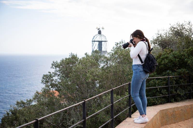 Mujer que toma la imagen de la playa del punto álgido con el faro borroso en el fondo imágenes de archivo libres de regalías