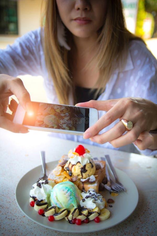 Mujer que toma la imagen del helado de Honey Toast con el teléfono elegante imagen de archivo