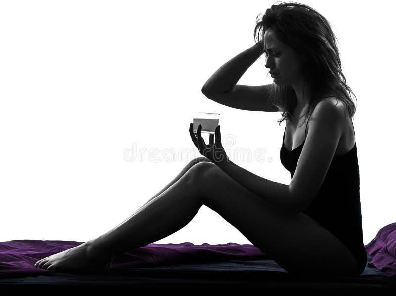 Mujer que toma la medicina efervescente en silueta de la cama imagen de archivo libre de regalías