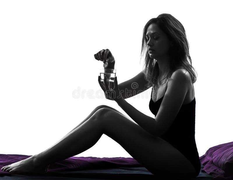 Mujer que toma la píldora que se sienta en silueta de la cama fotos de archivo