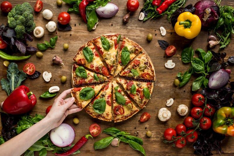 Mujer que toma la rebanada de pizza imagen de archivo libre de regalías