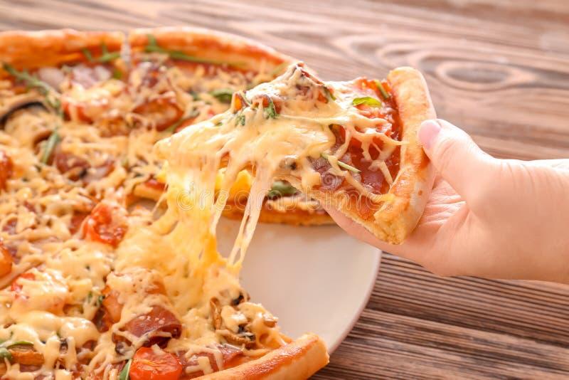 Mujer que toma la rebanada de pizza caliente sabrosa de la placa, primer imagen de archivo
