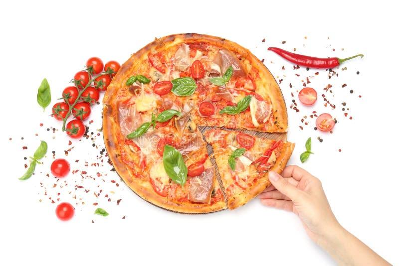 Mujer que toma la rebanada de pizza sabrosa con los tomates y la carne en el fondo blanco imágenes de archivo libres de regalías