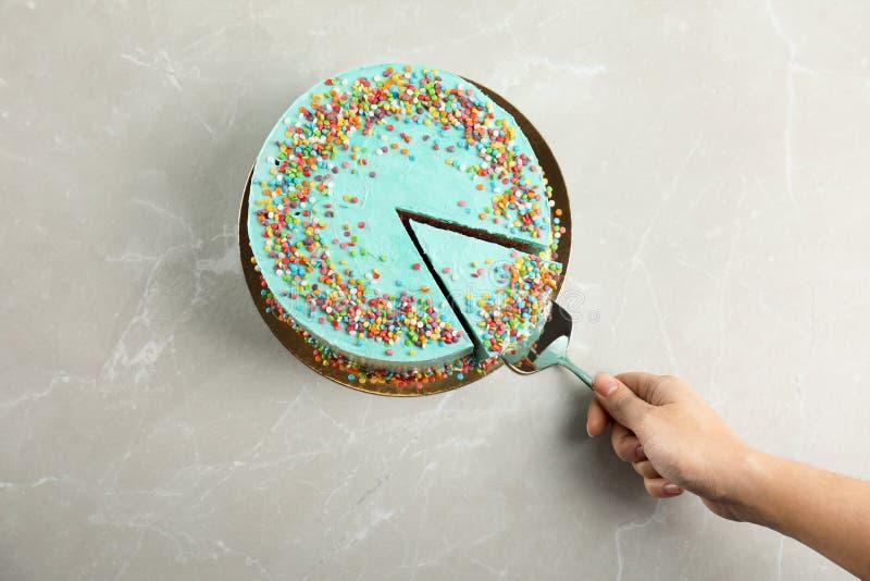 Mujer que toma la rebanada de torta de cumpleaños deliciosa fresca en la tabla fotografía de archivo libre de regalías