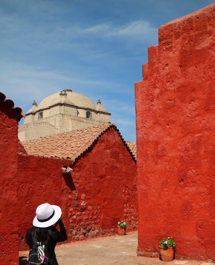 Mujer que toma las imágenes de los edificios vivos del color en Santa Catalina Monastery, Arequipa, sitio del patrimonio mundial  imagen de archivo