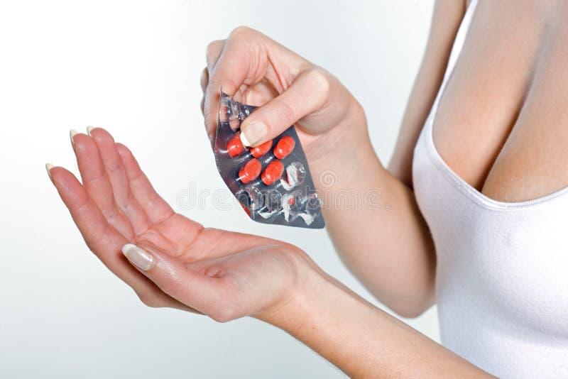 Mujer que toma las tabletas de pils de la medicina foto de archivo