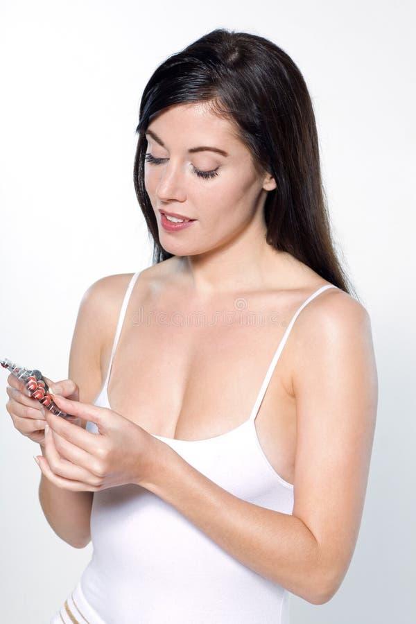 Mujer que toma las tabletas de pils de la medicina fotografía de archivo libre de regalías