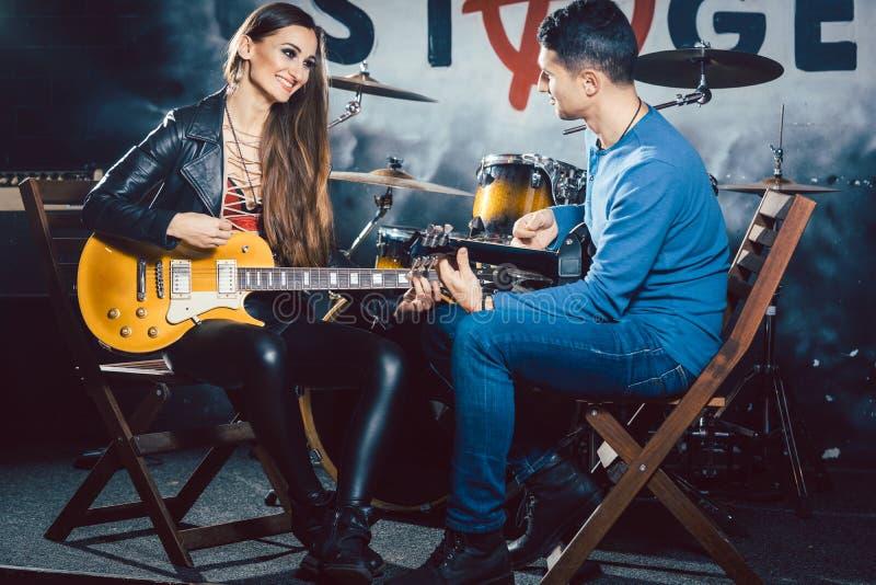 Mujer que toma lecciones de la guitarra con el profesor de música imagenes de archivo