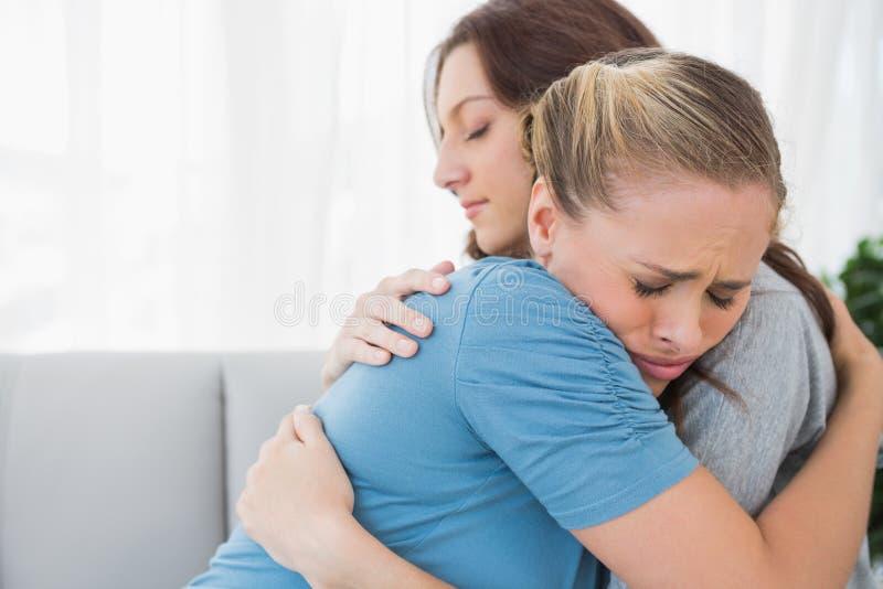 Mujer que toma a su amigo en sus brazos foto de archivo