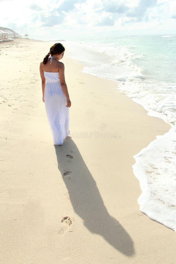 Mujer que toma un paseo en la playa y que se relaja imagen de archivo