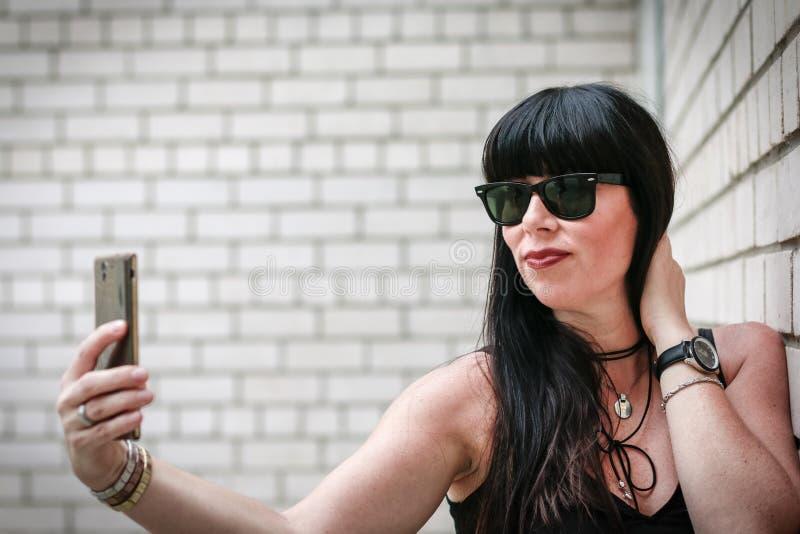 Mujer que toma un selfie cerca de una pared imagen de archivo libre de regalías