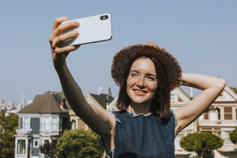 Mujer que toma un selfie con las señoras pintadas de San Francisco, los E.E.U.U. imágenes de archivo libres de regalías