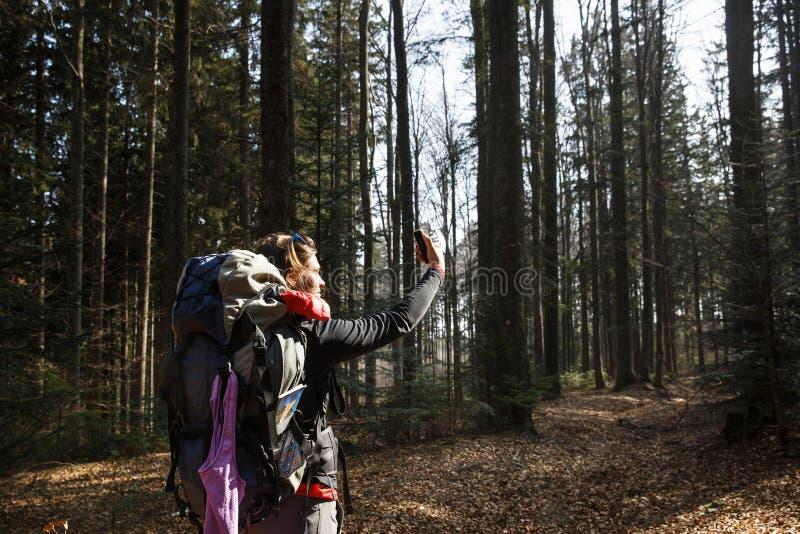 Mujer que toma un selfie en un alza a través del bosque imágenes de archivo libres de regalías