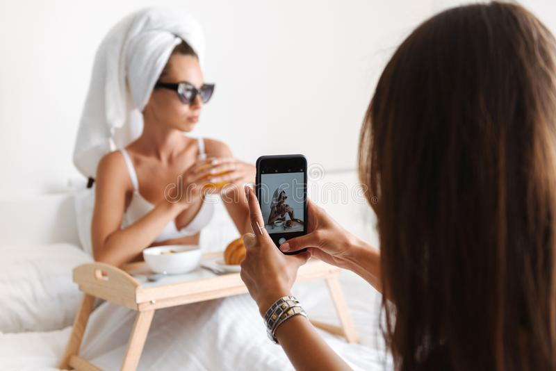 Mujer que toma una foto de una mujer de la celebridad en gafas de sol fotografía de archivo libre de regalías