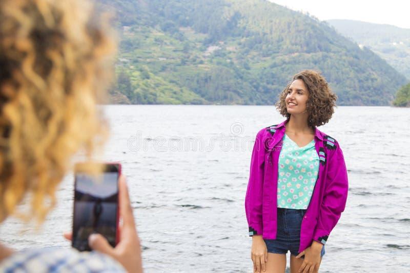 Mujer que toma una fotografía de un amigo foto de archivo