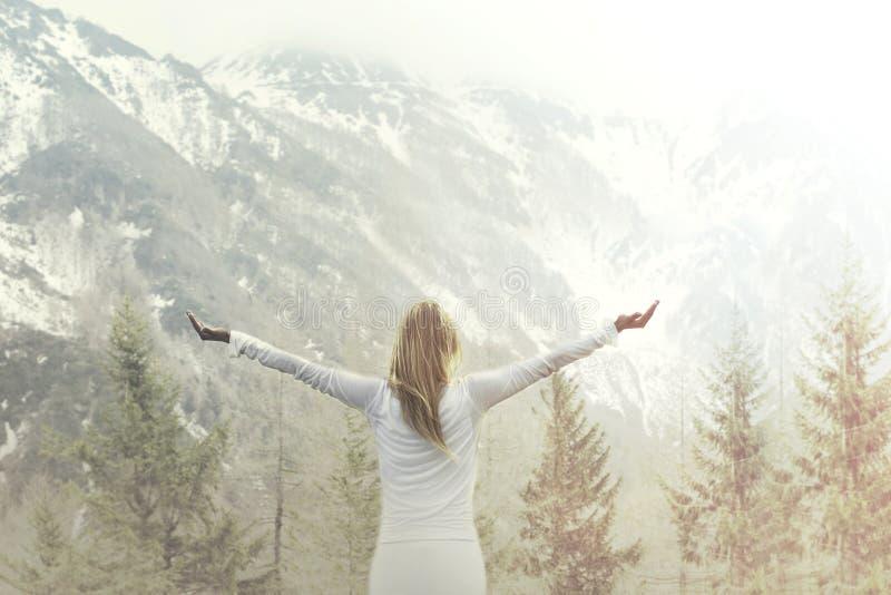 Mujer que toma una respiración delante de una montaña majestuosa fotos de archivo