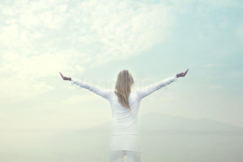 Mujer que toma una respiración delante de un cielo azul foto de archivo
