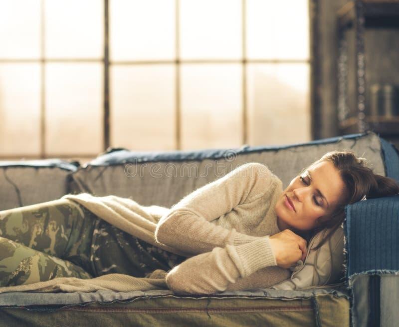 Mujer que toma una siesta en un sofá en un desván de la ciudad imagen de archivo libre de regalías