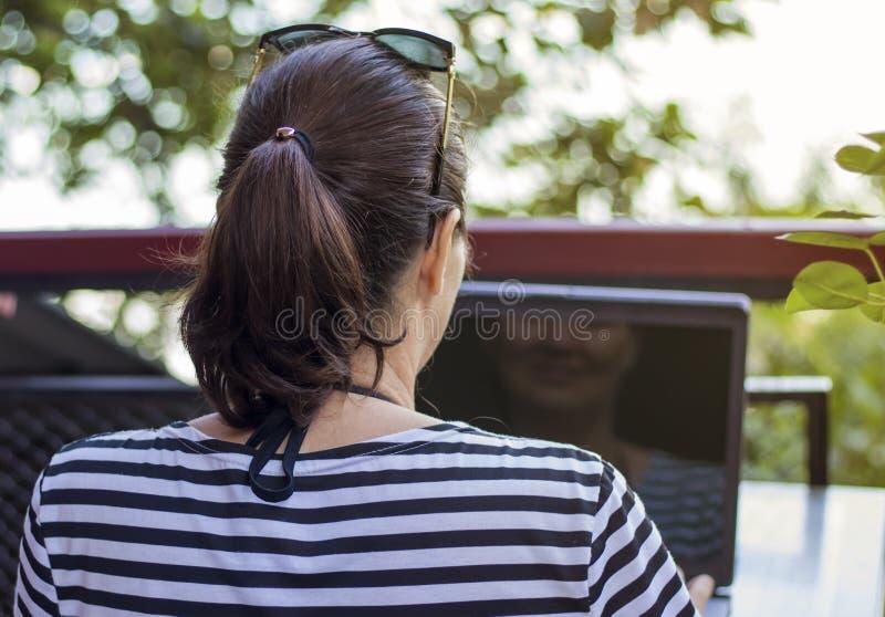 Mujer que trabaja con el ordenador portátil en balcón del verano foto de archivo