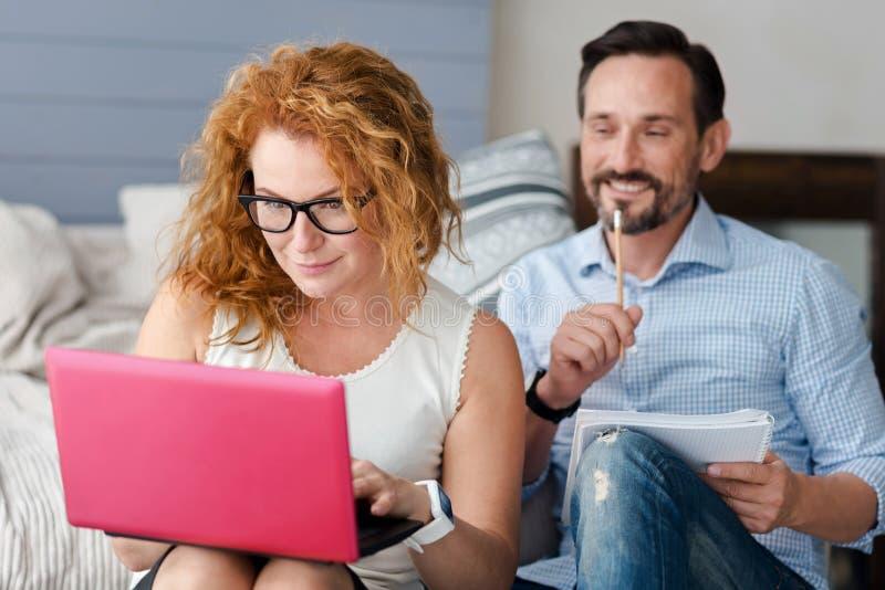 Mujer que trabaja con el ordenador portátil mientras que hombre que toma notas foto de archivo