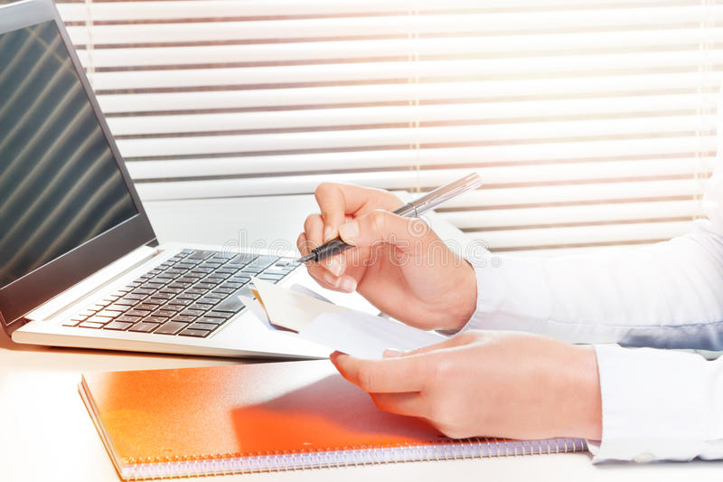 Mujer que trabaja con los papeles y que hace notas imagen de archivo