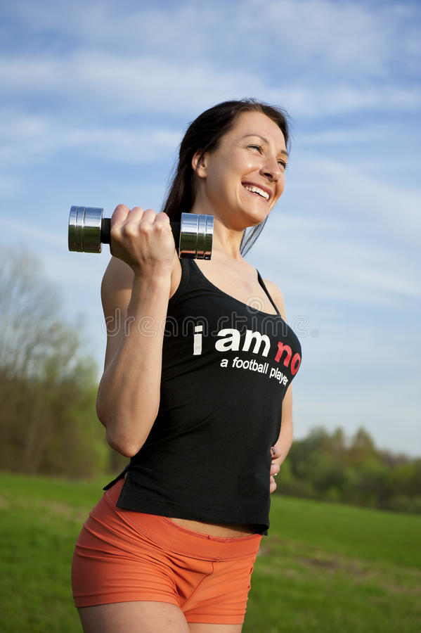 Mujer que trabaja con pesa de gimnasia