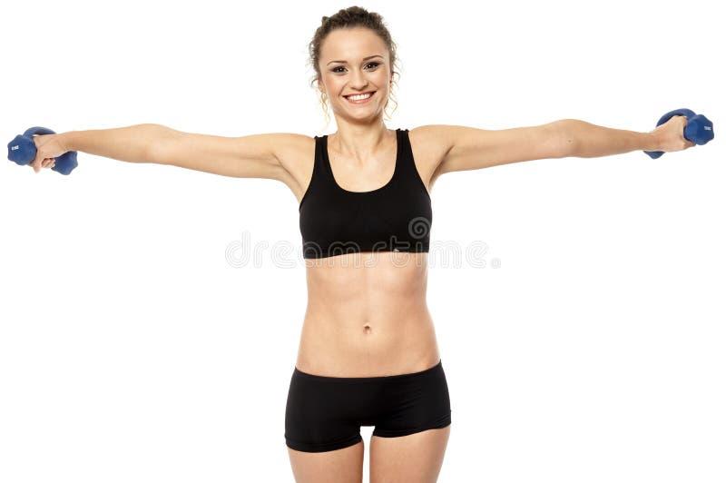Mujer que trabaja con pesas de gimnasia imagen de archivo libre de regalías