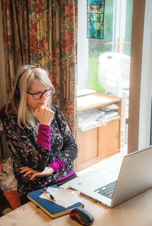 Mujer que trabaja del hogar, el escuchar webinar en su ordenador portátil, auriculares que llevan fotos de archivo libres de regalías