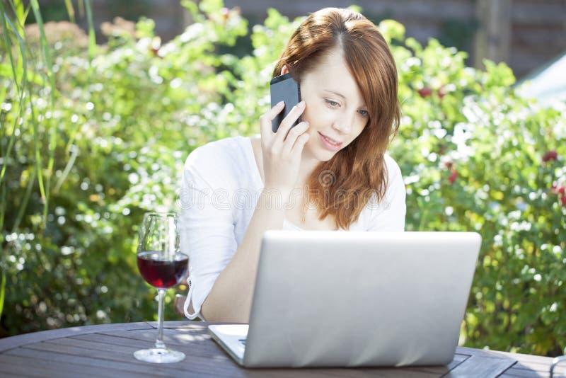 Mujer que trabaja del hogar que se sienta al aire libre imagenes de archivo