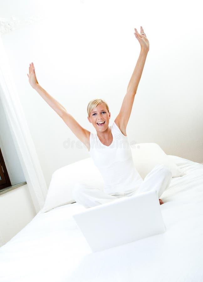 Mujer que trabaja en cama foto de archivo