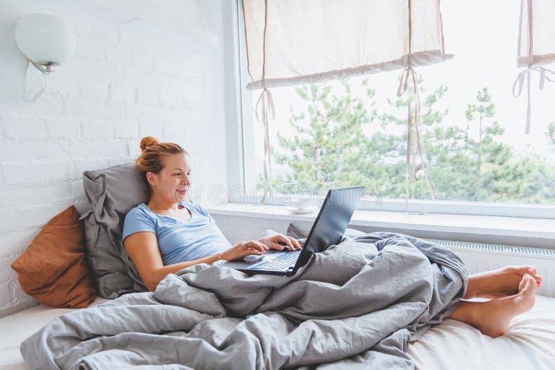Mujer que trabaja en cama en el ordenador portátil temprano por la mañana imagen de archivo libre de regalías