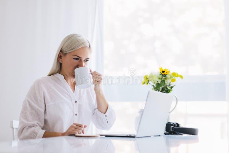 Mujer que trabaja en casa en un ordenador portátil fotos de archivo libres de regalías