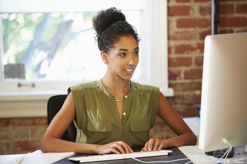 Mujer que trabaja en el ordenador en oficina contemporánea imagen de archivo libre de regalías