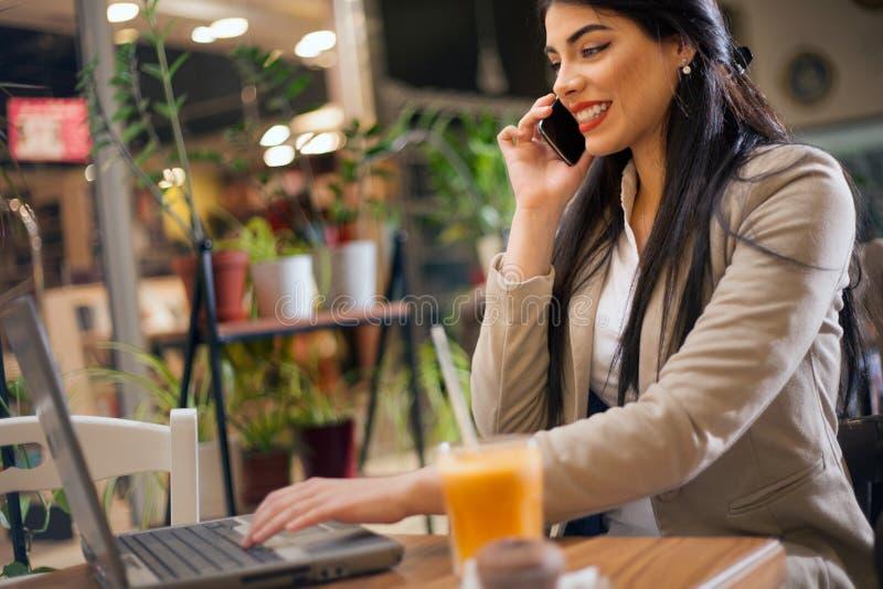 Mujer que trabaja en el ordenador portátil en cafetería imágenes de archivo libres de regalías